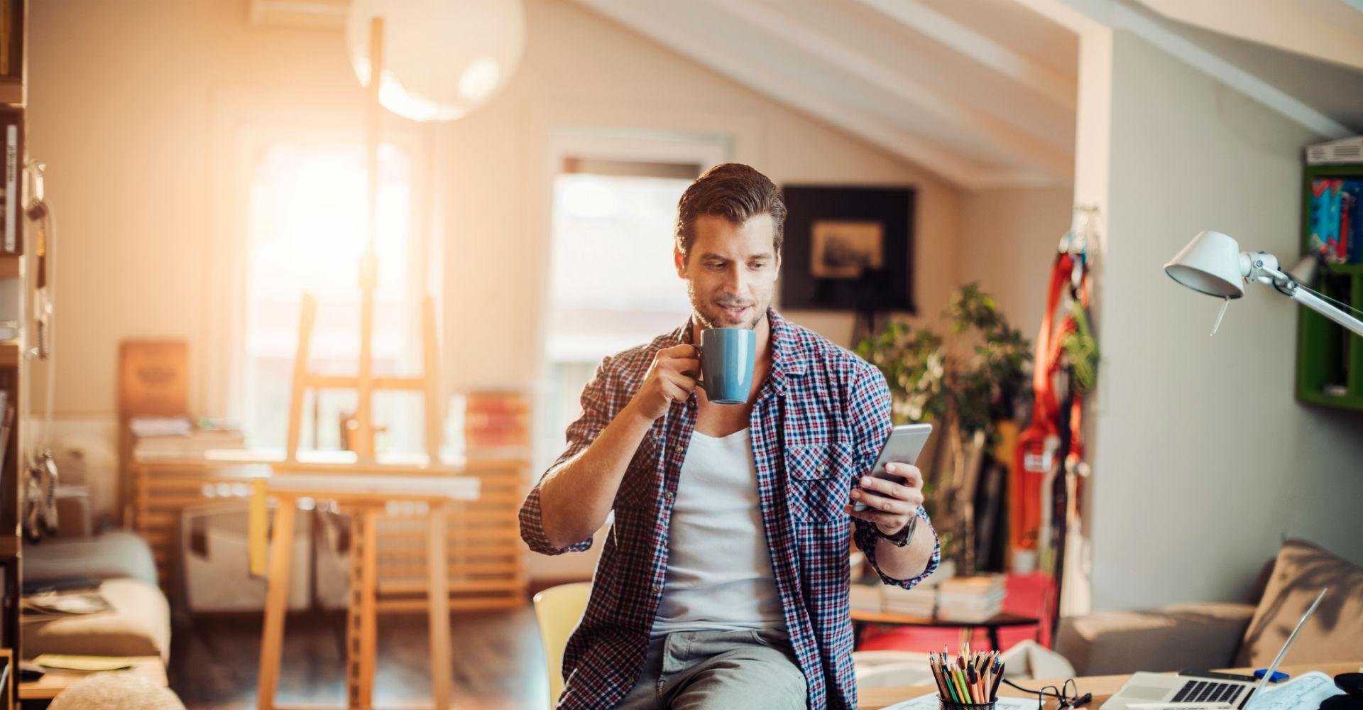 Mann steuert sein smartes Zuhause über sein Smartphone.