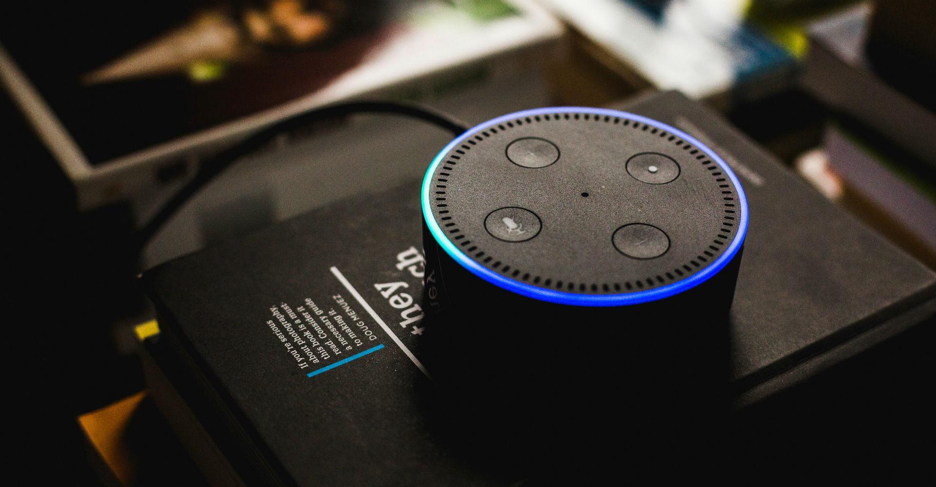 Der schwarze Amazon Echo Dot auf einem Stapel Bücher.