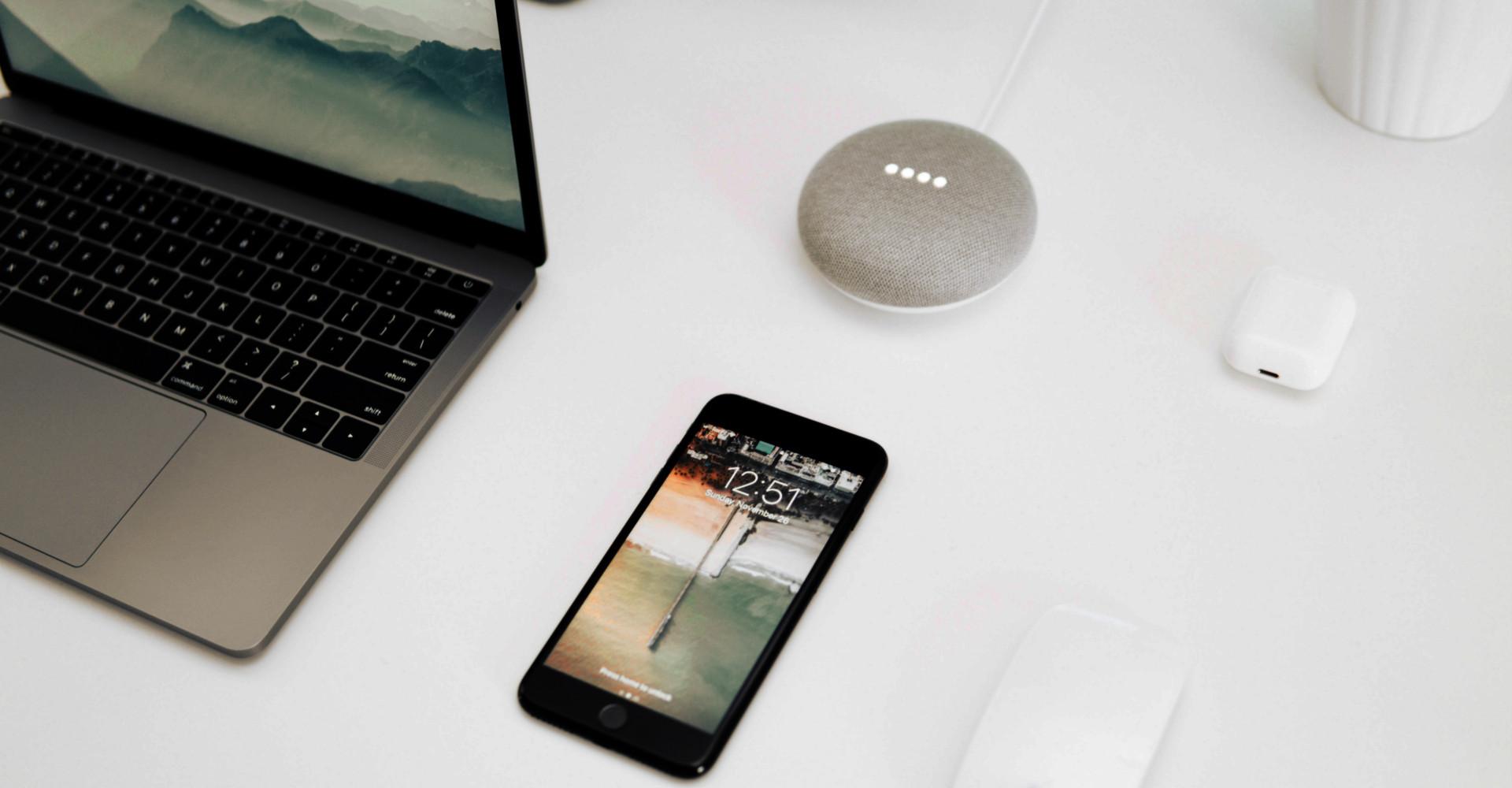 Google Smart Home Mini, ein Laptop und ein Smartphone