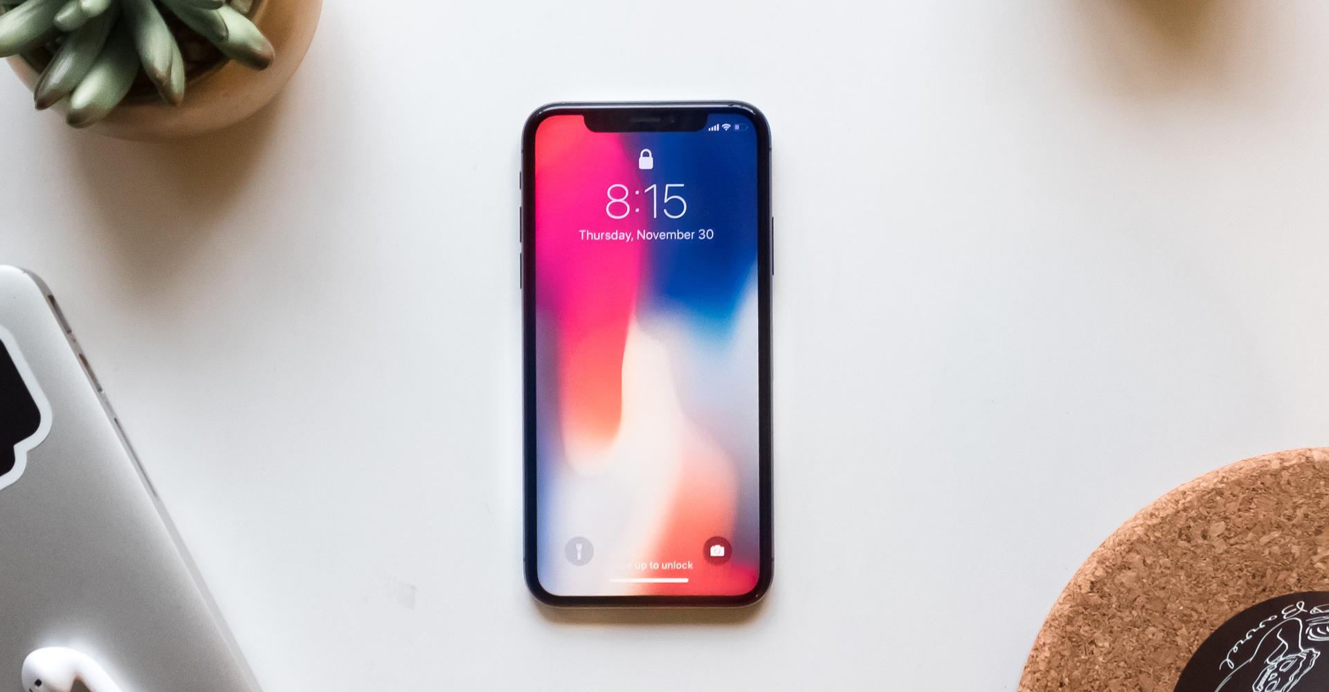 Das neue iPhone X liegt auf einem weißen Schreibtisch.