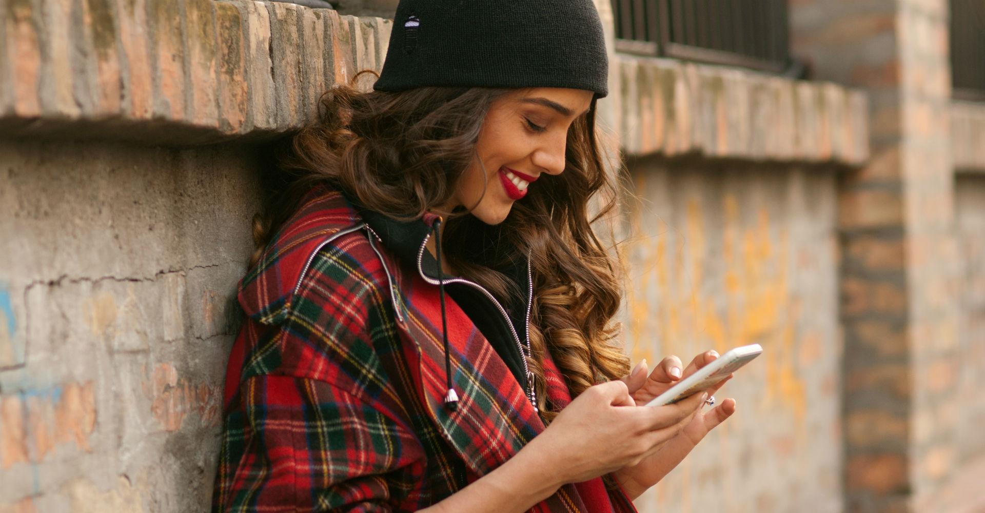 Junge Frau in kariertem Hemd schaut auf Smartphone.