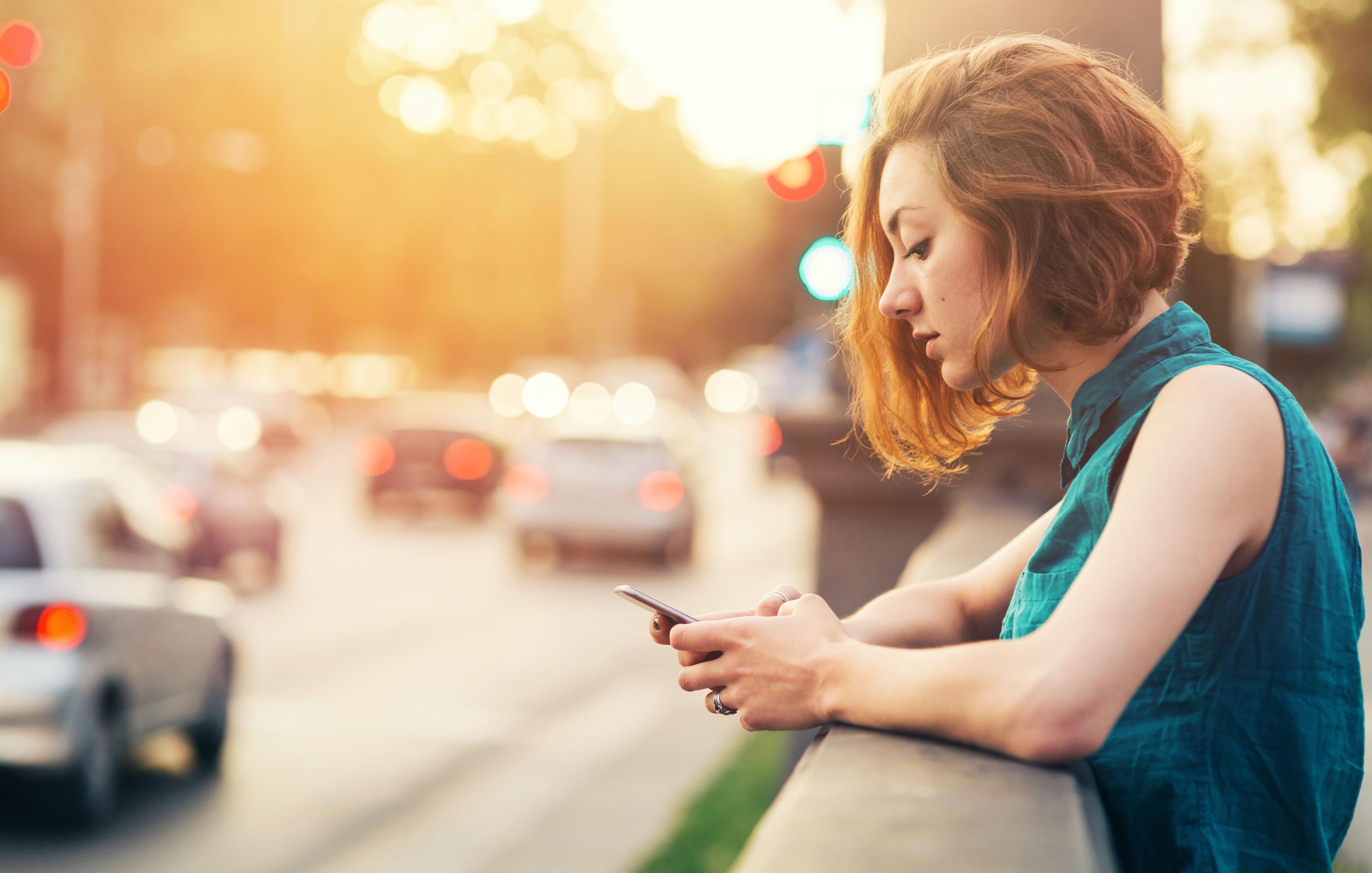 Junge Frau mit roten Haaren lehnt sich an eine Mauer und schaut auf ihr Smartphone.