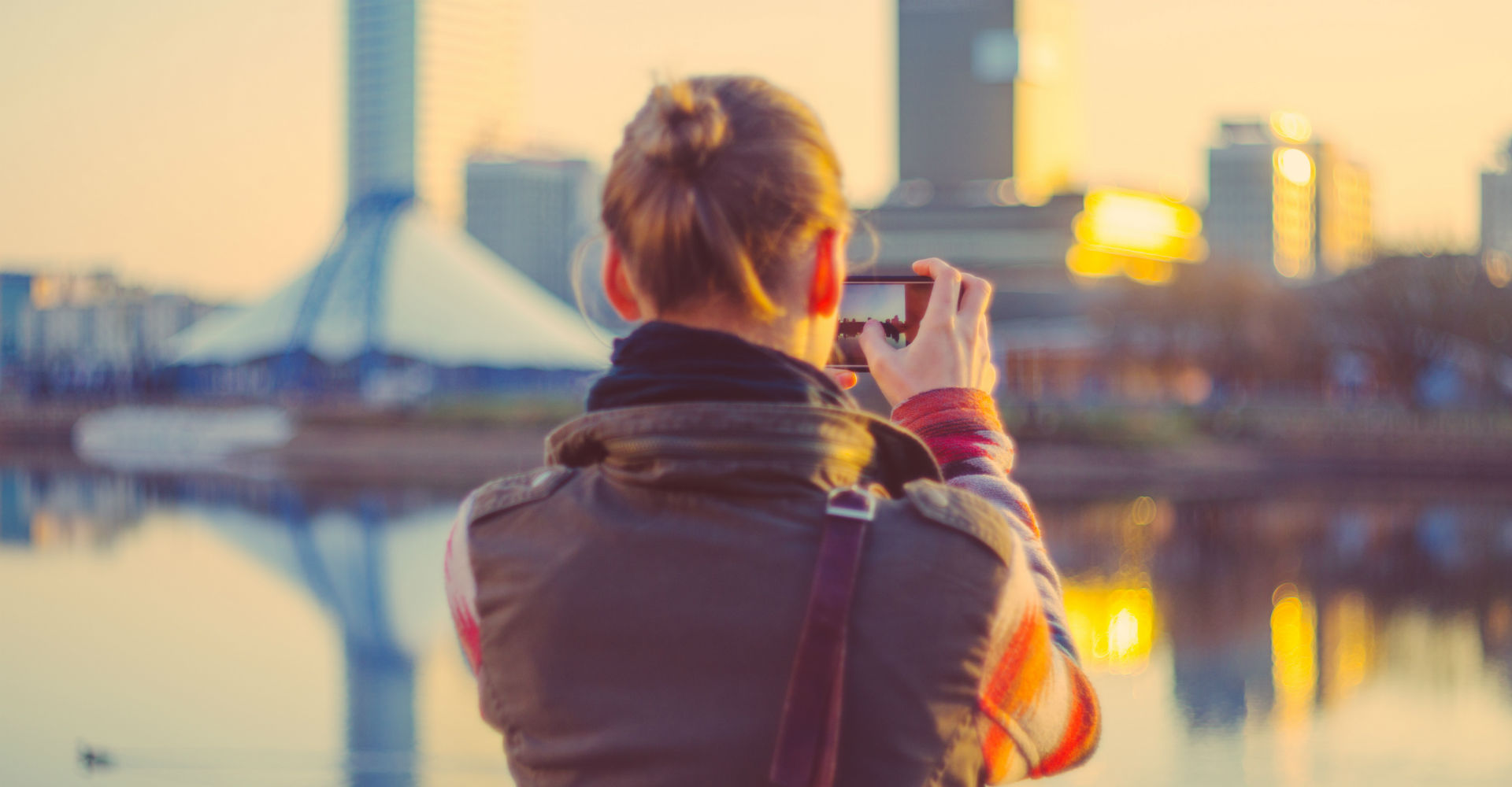Junge Frau macht ein Video von der Großstadt mit dem Smartphone.